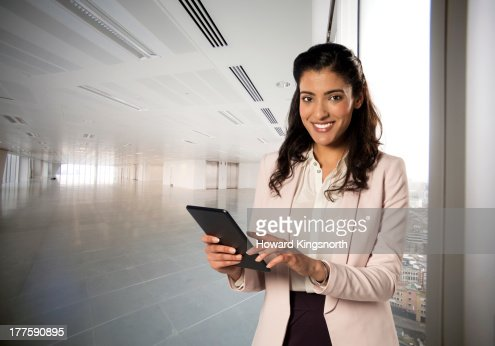 young female with tablet in empty office : Stock Photo