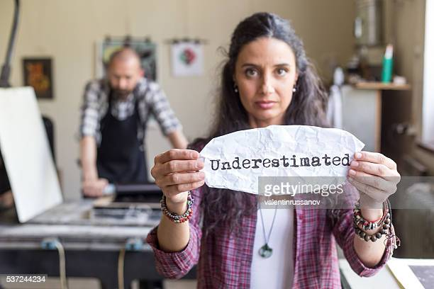 Young female worker holding a sign 'underestimated'
