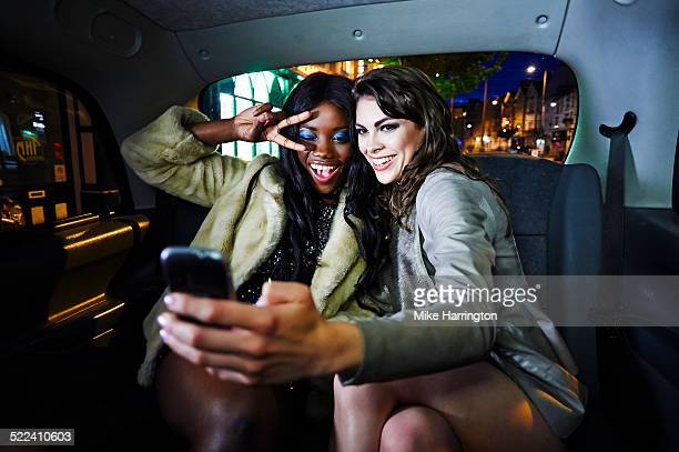 Young females taking selfie in back of taxi