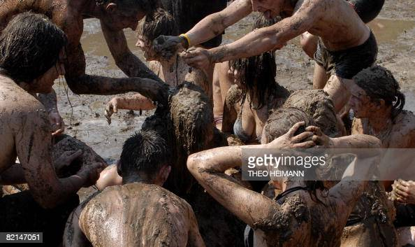 Young festival visitors enjoy a bath in the mud during the 'Przystanek Woodstock' music festival in the western Polish town of Kostrzyn nad Odra on...