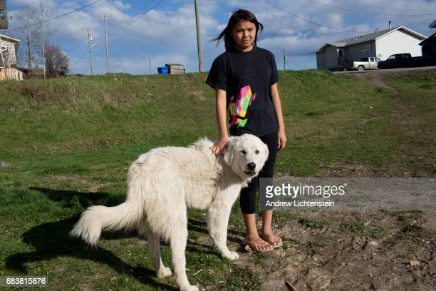 Young First Nation walks down a street with her protective dog on April 25 2016 in the small community of Taiche British Columbia Three years after...