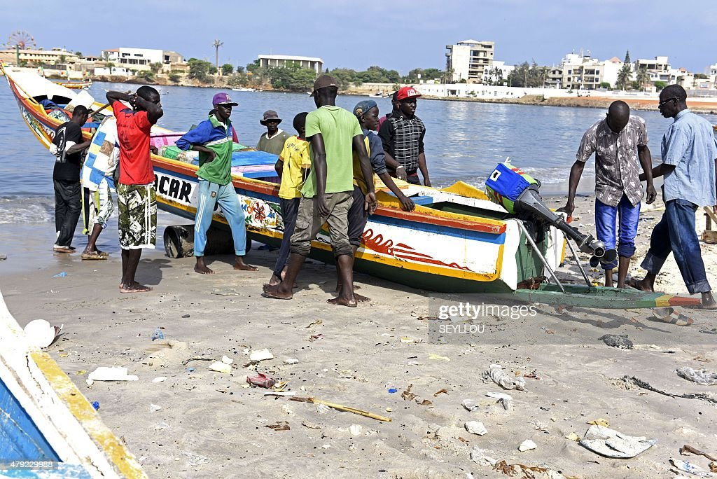 Young fishermen pull a wooden pirogue to the shore of the traditional fishing harbour of Soumbedioune in Dakar on July 2 2015 The fishermen's...
