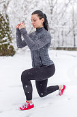 Young fit caucasian woman doing lunge exercise in snow at winter, eyes closed, outdoors
