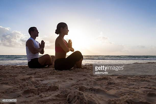 Young fit couple meditating on the beach at sunrise