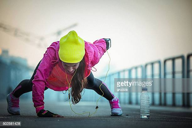 Young fit determined woman exercising push-ups on one hand