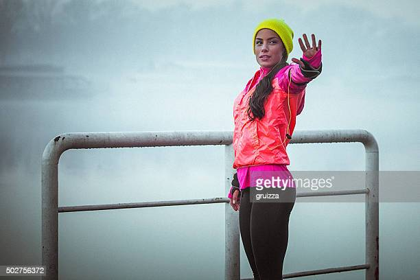 Young fit determined woman stretches her hand after work out