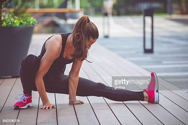 Young fit determined woman stretches her leg after work out