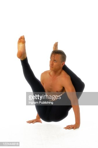 A young fit man practices Yoga.