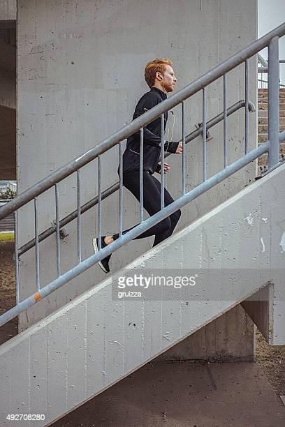 Young fit homme courir dans un environnement urbain