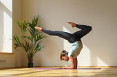 young flexible woman handstand and doing gymnastic exercise at home, natural light