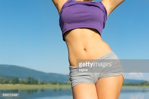 Young fit woman's belly outdoors in summer : Stock Photo