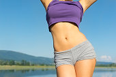 Closeup of young fit woman's belly outdoors in summer. Fitness girl in gray shorts and purple tank top outdoors at the beach on sunny summer day. No retouch, developed from RAW, vibrant colors, natura