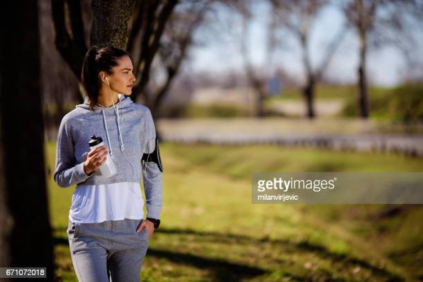Young fitness girl resting in city park