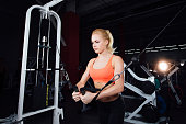 young fitness woman demonstrate crossover exercises. The pectoral muscles, hard training with exercise-machine Cable Crossover in gym