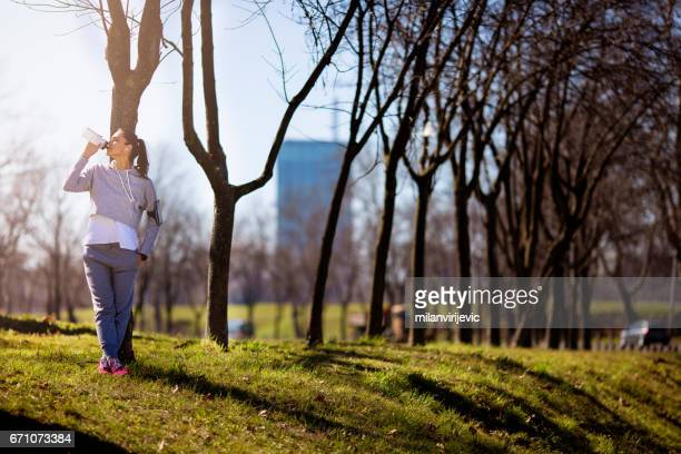 Young fitness woman drinking water in nature