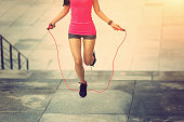 young fitness woman jumping rope on city