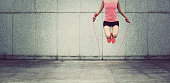 young fitness woman jumping rope outdoor