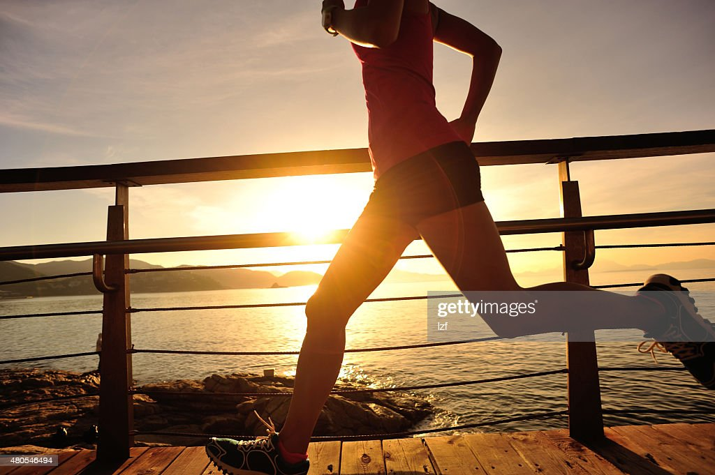 young fitness woman legs running on seaside wooden boardwalk : Stock Photo