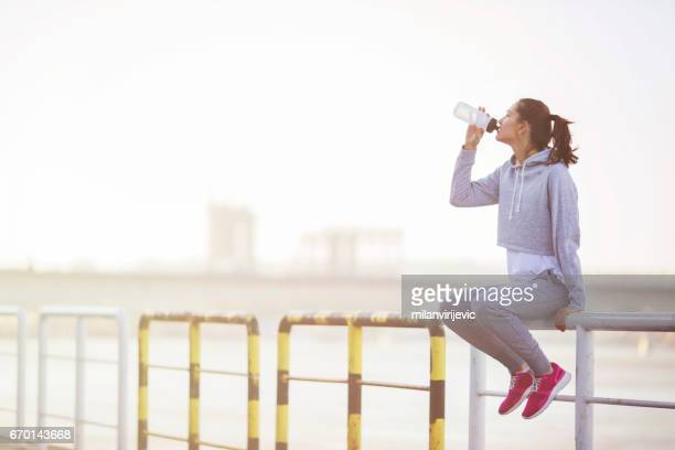 Young fitness woman resting after running and drinking water