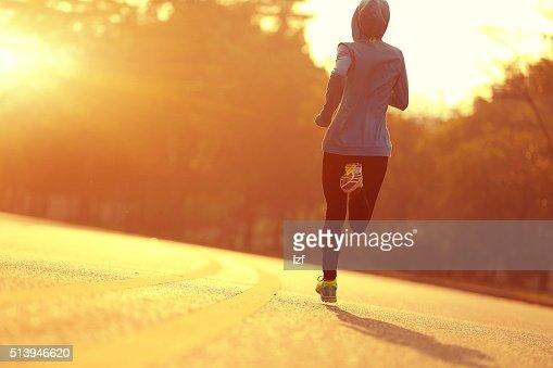Jovem aptidão mulher de corredor atleta a correr em estrada ao nascer do sol : Foto de stock