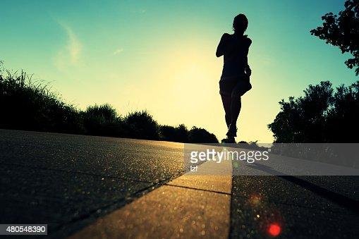 Jovem mulher de fitness em execução no nascer do sol de trail : Foto de stock