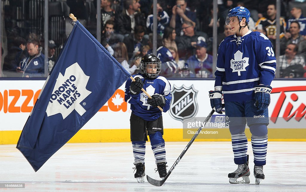 A young flag bearer looks up to Matt Frattin #39 of the Toronto Maple Leafs during the pre game ceremony prior to a game between the Boston Bruins and the Toronto Maple Leafs on March 23, 2013 at the Air Canada Centre in Toronto, Ontario, Canada. The Leafs defeated the Bruins 3-2.