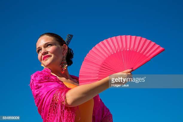 Young flamenco dancer holds fan at Plaza de Espana
