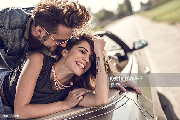 Young flirty couple enjoying in their love on a convertible.