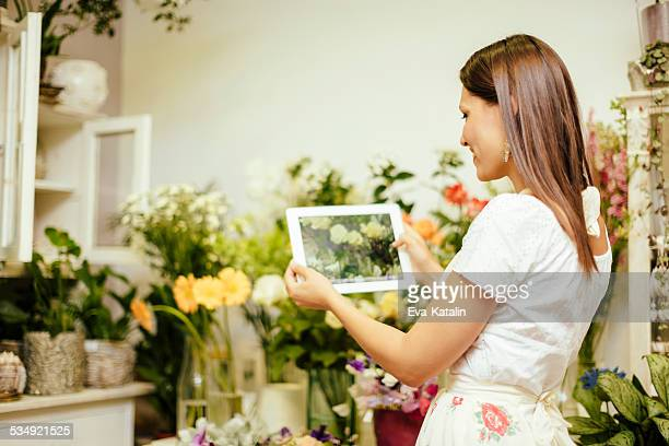 Young florist takes pictures in her shop