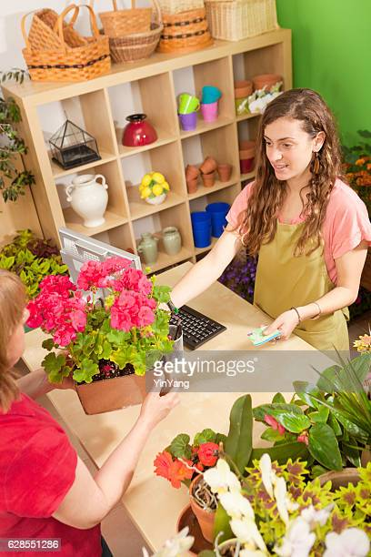 Young Flower Garden Center Sales Person Serving Retail Customer