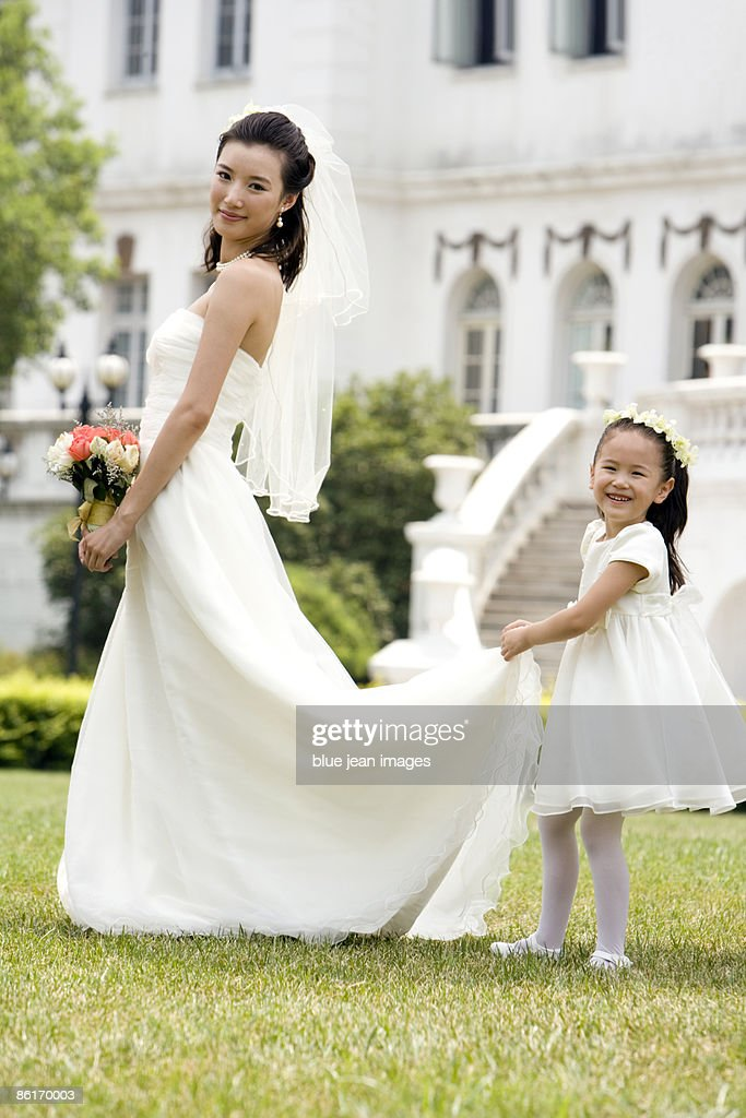 A young flower girl with the bride after a wedding