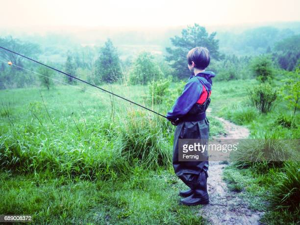 Young fly-fisherman looking out on a trout stream