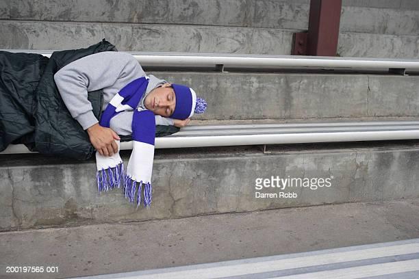 Young football fan asleep in sleeping bag on stadium bench