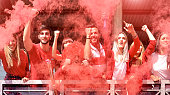 Young football supporter fans cheering with colored smoke watching soccer match together at stadium - Friends people group with red t-shirts having excited fun on sport world championship concept