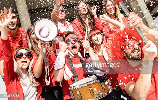 Young football supporter fans cheering with flag and confetti watching soccer match at stadium - Friends people group with red t-shirts having excited fun on sport world championship concept : Foto de stock
