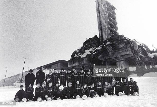 Young footballers involved with Inter Campus Project pose for a photo in front of the Sarajevo's TV building destroyed during the war February 5 2001...
