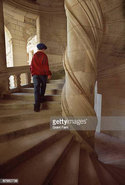 young french boy walking up chateau stone stairs