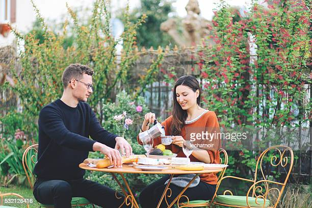 Young French couple eating in the garden home