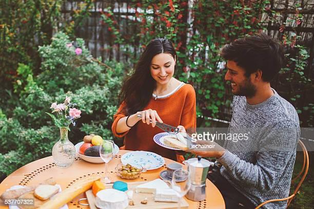 Francés Pareja joven teniendo un brunch dominical en el jardín