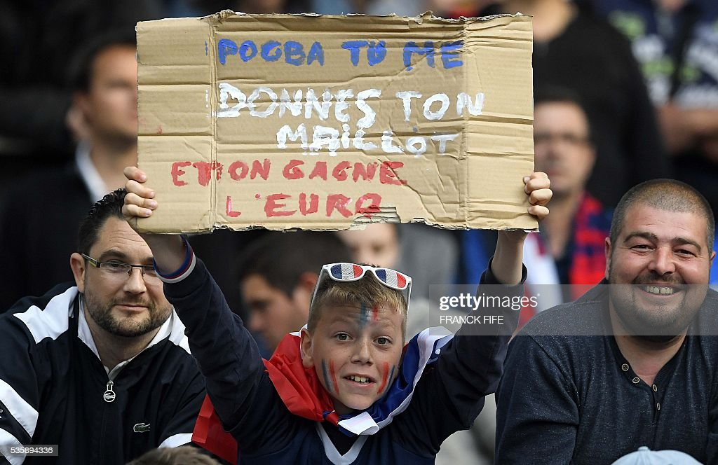 A young French supporter holds a placard reading 'Pogba to me, give me your jersey and we win the Euro championship' as he attends the International friendly football match between France and Cameroon at the Beaujoire stadium, in Nantes, western France, on May 30, 2016 as part of the French team's preparation for the upcoming Euro 2016 European football championships. / AFP / FRANCK