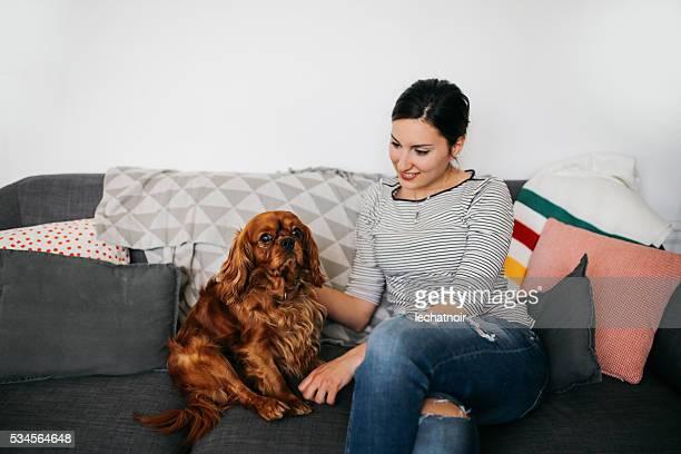 Français jeune femme se détendant sur le canapé en jouant avec chien