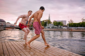 Young friends about to jump into the lake. Young men running on a jetty.