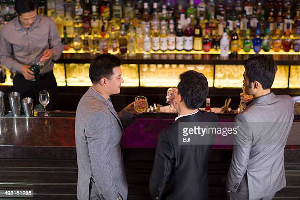 Young friends chatting at bar