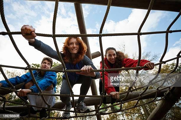 Young friends climbing assault course equipment