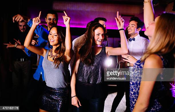 Young friends dancing in a group in a night club