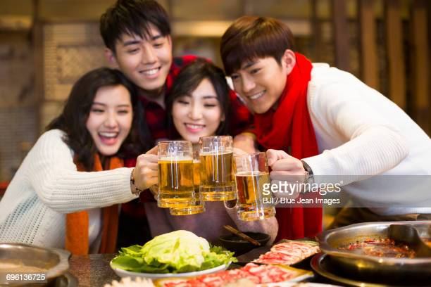 Young friends drinking beer in hotpot restaurant