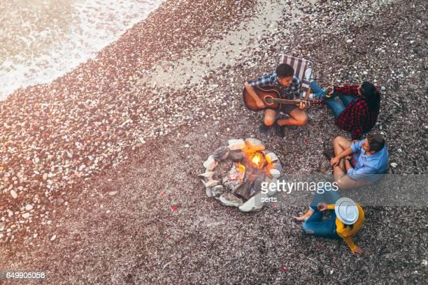 Jeunes amis appréciant la musique près de feu de camp