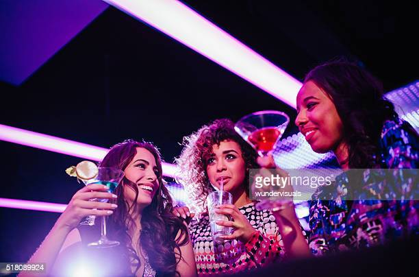 Young friends enjoying party with drinks at the club