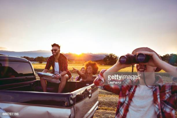 Young friends enjoying the freedom on a Car Trip over a country offroad