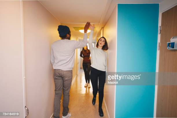 Young friends giving high-five walking in corridor of college dorm